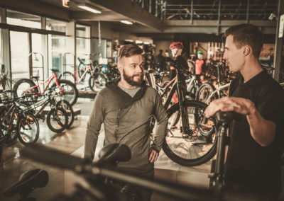 Salesman showing a new bicycle to interested customer in bike sh